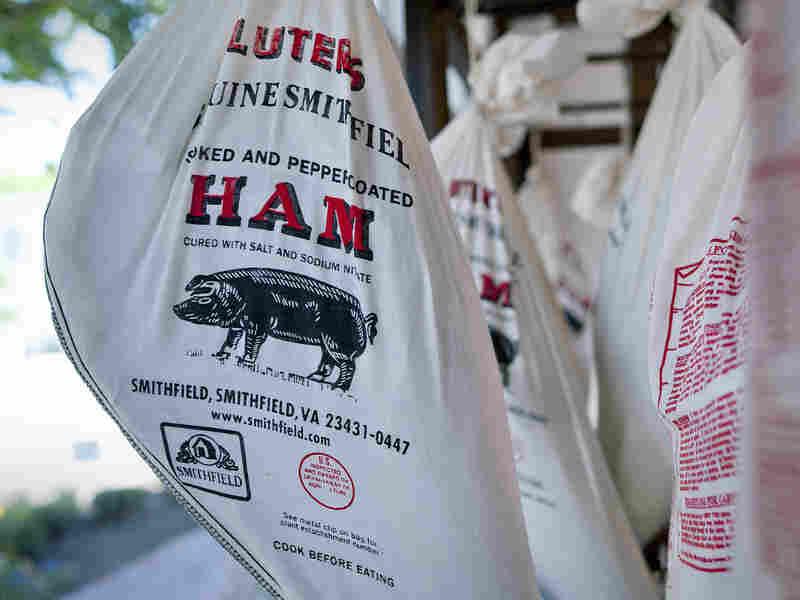 Smithfield hams hang outside the Taste of Smithfield restaurant and gourmet market in Smithfield, Va. Shuanghui International Holdings plans to buy Smithfield Foods, the world's biggest hog producer.