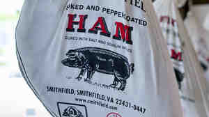 Smithfield hams hang outside the Taste of Smithfield restaurant and gourmet market in Smithfield, Va. Shuanghui International Holdings plans to buy Smithfield Foods, the world's biggest hog producer.