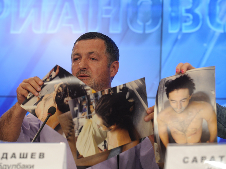 Abdul-Baki Todashev, father of Ibragim Todashev, shows pictures he says are of his son's bullet-riddled body, at a news conference in Moscow on Thursday.