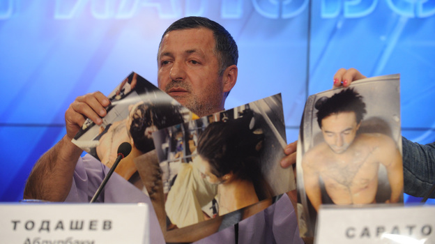 Abdul-Baki Todashev, father of Ibragim Todashev, shows pictures he says are of his son's bullet-riddled body, at a news conference in Moscow on Thursday. (AFP/Getty Images)