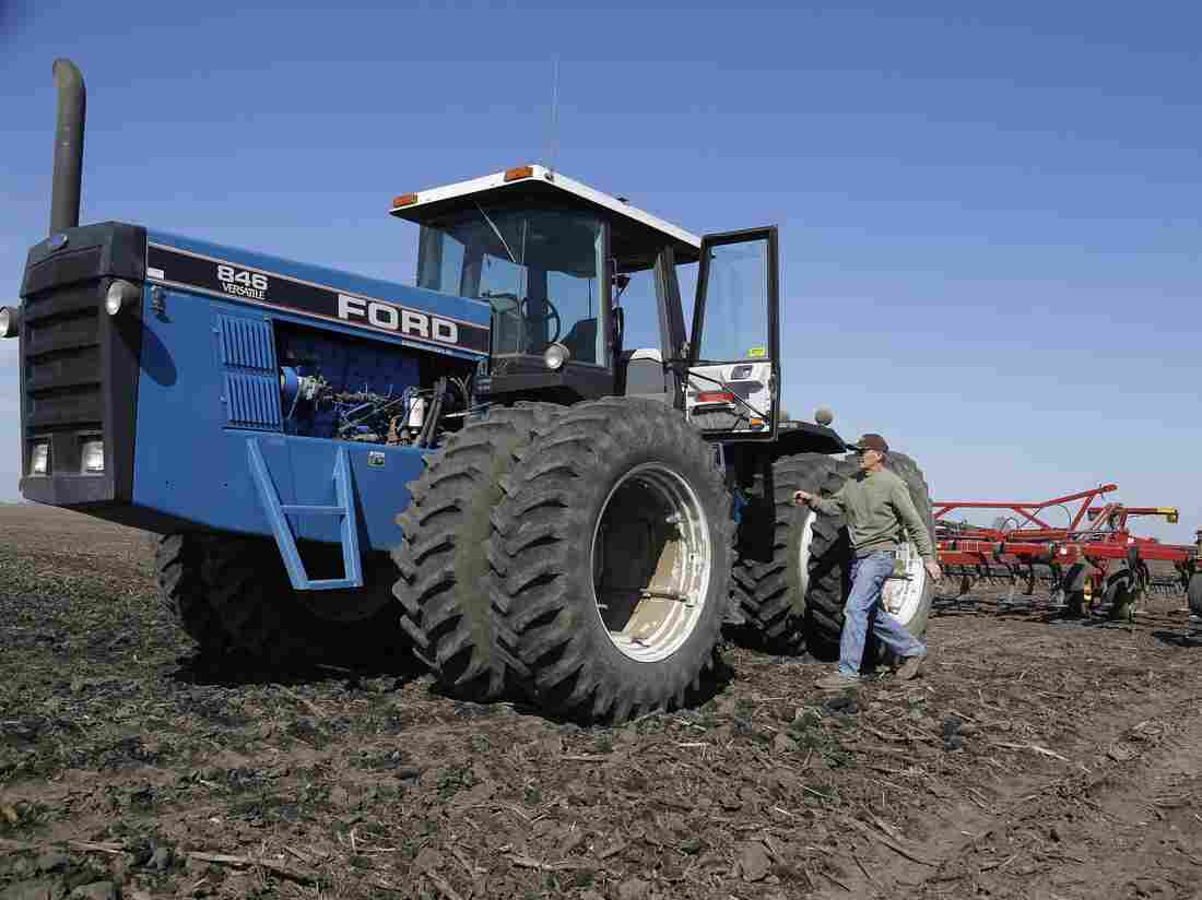 An Illinois corn and soybean farmer walks to his tractor while cultivating his field.