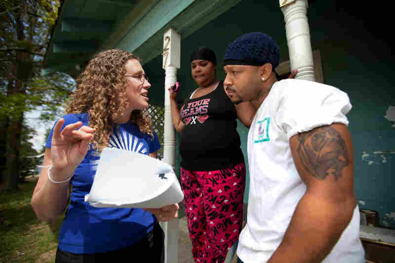 Anna Hrybyk (left) talks with Standard Heights neighborhood residents Terrica Hardnett (middle) and Terrell Sylvas about the current state of the EPA's investigation into the Exxon Mobil plant.