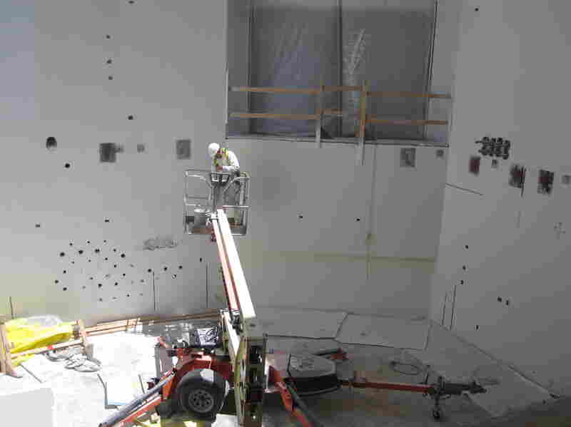 A construction worker paints walls at the Maryland Proton Treatment Center in Baltimore. Each of the center's five rooms will contain a massive piece of equipment that will rotate around a cancer patient to deliver a special kind of radiation.