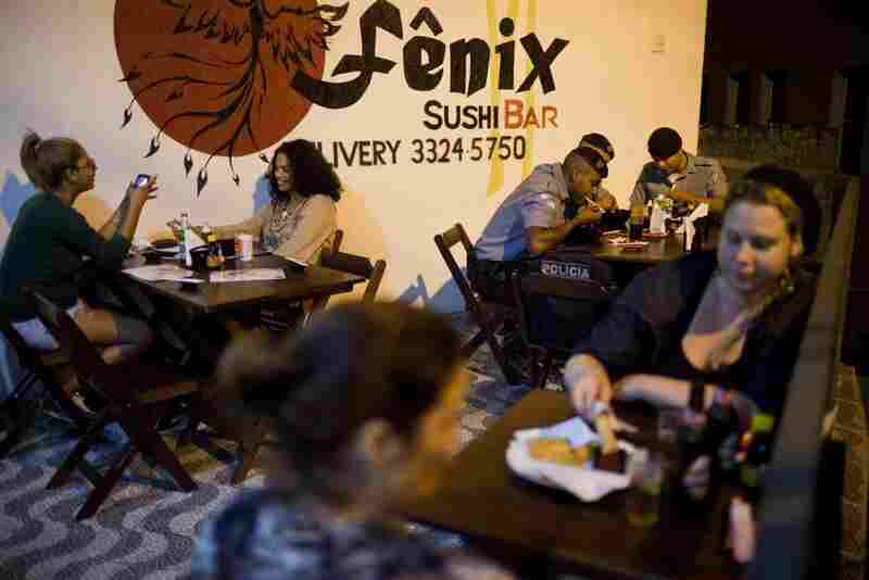 Members of the Pacification Police dine with local residents at the Fenix Sushi Bar in the favela Vidigal. The sushi bar is just one of several new businesses that attract people to the favela.