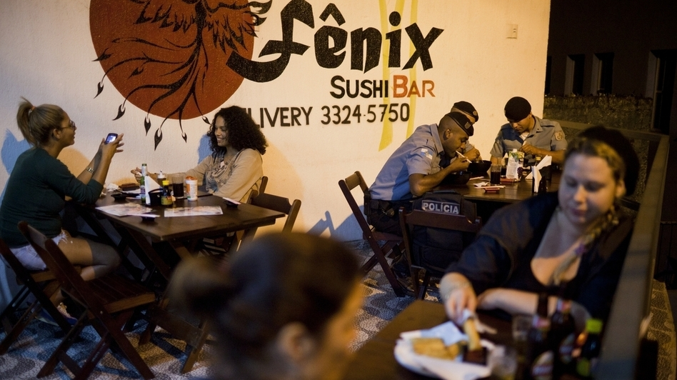 Members of the Pacification Police dine with local residents at the Fenix Sushi Bar in the favela Vidigal. The sushi bar is just one of several new businesses that attract people to the favela. (Lianne Milton for NPR)