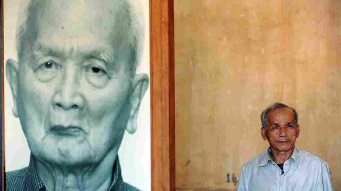 """A Cambodian survivor of the infamous Tuol Sleng prison (known as S-21) poses by a picture of """"Brother Number Two"""" Nuon Chea last year."""