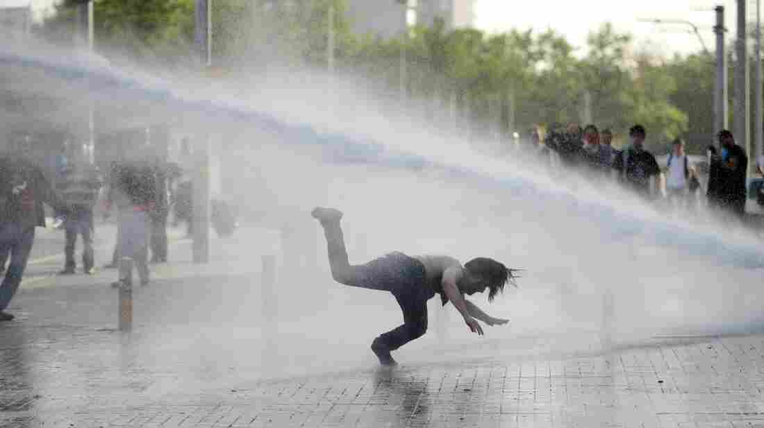 Demonstrators flee from a water cannon during clashes with riot police Friday during a protest against the demolition of Taksim Gezi Park, in Taksim Square in Istanbul.