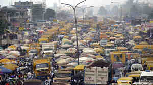 People walk struggling for space between public transport buses and trucks at the burstling Oshodi bus stop in Lagos 06 Februa