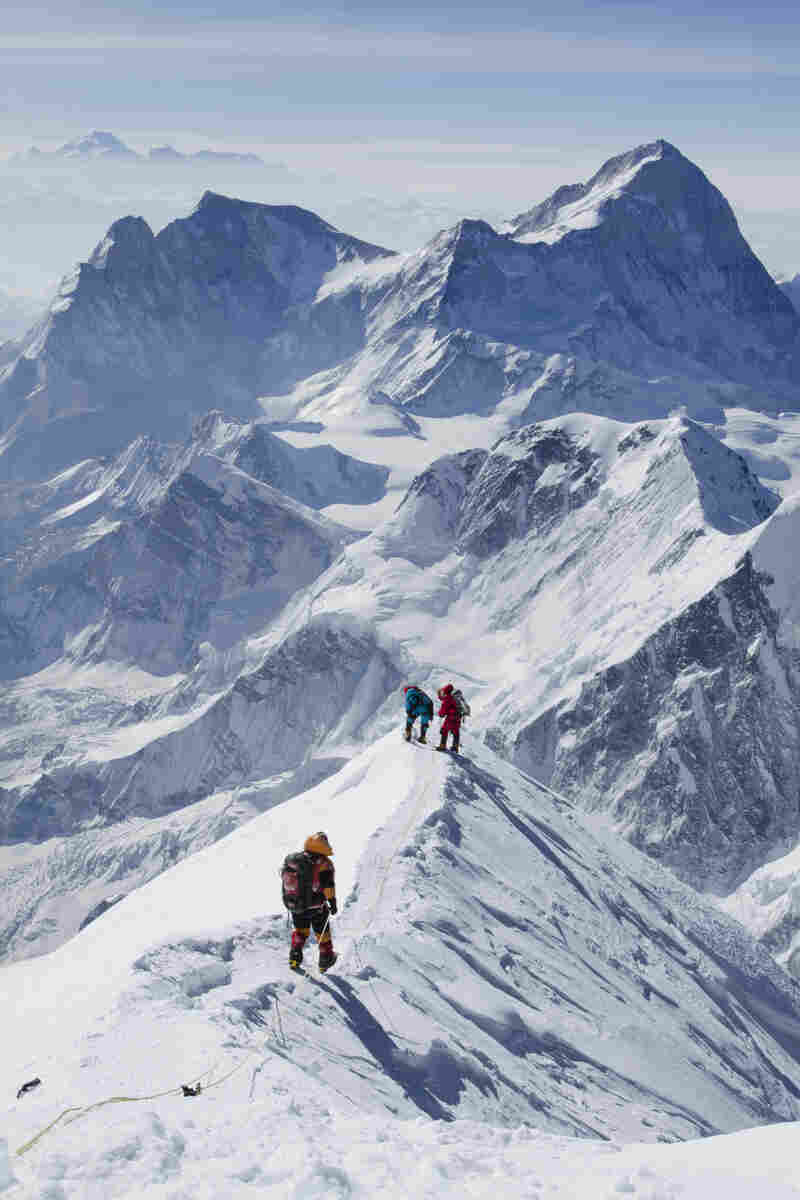 Members of the South Col Five walk along the corniced ridge of the South Summit after their successful climb. Makalu Peak rises in the background at right, and Kanchenjunga can be seen in the distance. The team had a good day to summit; the low-lying clouds are a sign of stable weather.