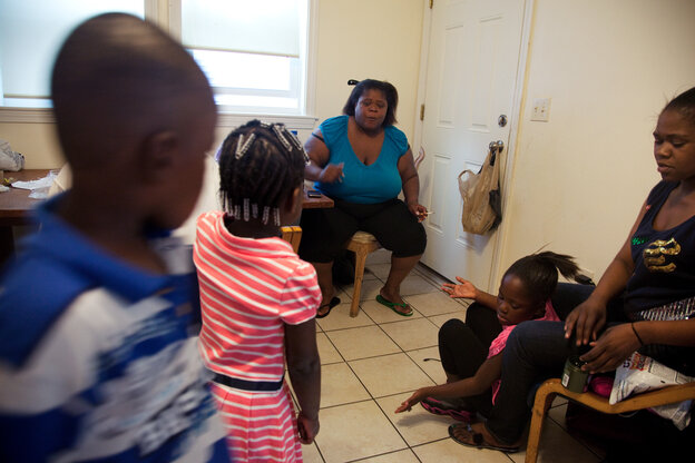 """Michelle Williams (center), at home in Dorchester, Mass., talks with grandchildren Ayniah Williams (pink dress) and Drequain Smith (far left). At right are her daughters Vanessa """"Nessa"""" Williams (far right) and Margaret Williams. Both Michelle and Ayniah had latent TB infections and have been treated."""