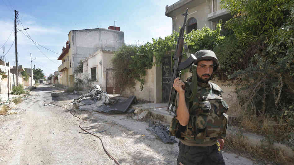 A Syrian soldier walks through the hotly contested city of Qusair on May 22. The Syrian army, backed by Lebanon's Hezbollah militia, has been waging a fierce fight with rebels in the key western city for the past two weeks.