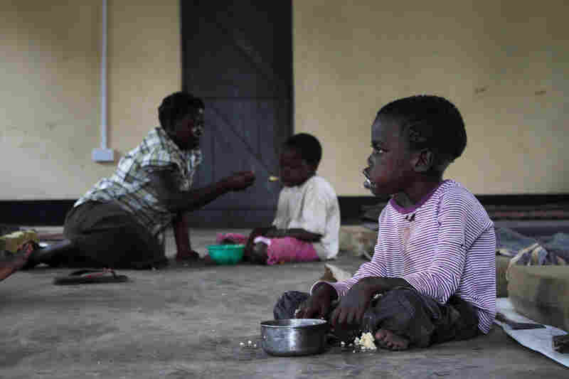 Two children who have nodding syndrome eat a meal at Atanga.