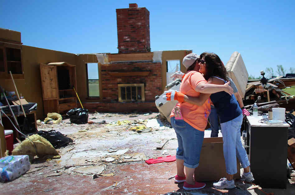 Tammy Wade (left) is hugged by Dana Givens in what is left of her home in El Reno, Okla., on Sunday, after it was destroyed by a tornado.