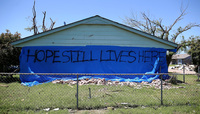 "A sign proclaiming ""Hope Still Lives Here"" is posted on the side of a damaged home in Moore, Okla."