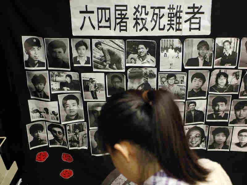 A woman reads a book in front of portraits of Tiananmen victims at the June 4 Memorial Museum run by pro-democracy activists at City University in Hong Kong on Monday, the eve of the 24th anniversary of the crackdown.