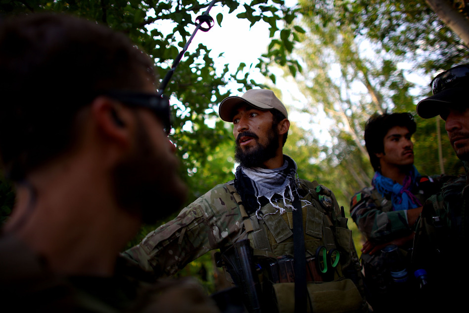 Capt. Nasir (center) talks with members of Green Berets before a shura in Kasan. The mission of the Green Berets and ANASF is to recruit more Afghan local police to act as an armed neighborhood watch that will serve as the first line of defense against the Taliban. (NPR )