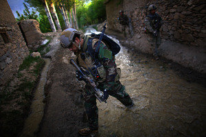 U.S. Green Berets patrol up a flooded stream with ANASF.