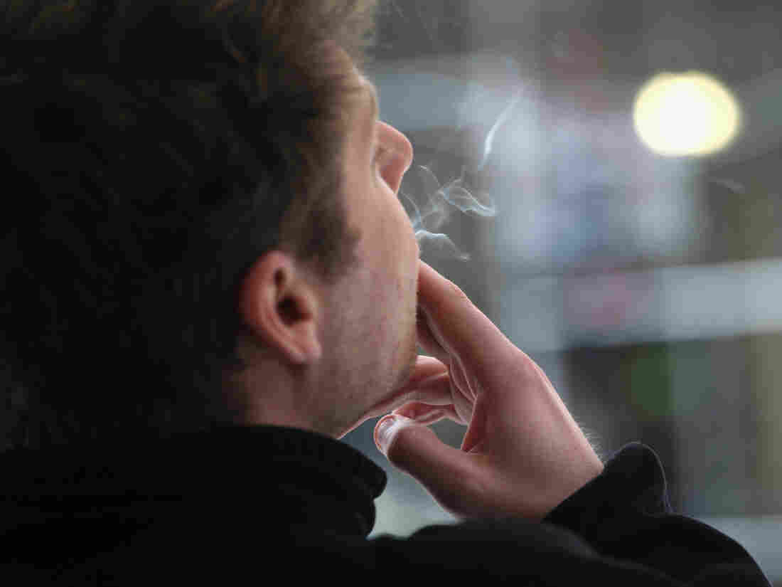 A man smokes outside an office building in New York City in April. Smoking breaks cost employers almost $3,000 per year per smoking employees, a study says.