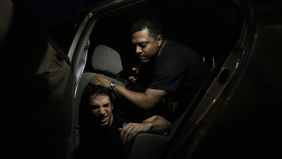 Two men participate in a kidnapping drill in an intensive self-defense course at the School of Personal Protection in Caracas. In 2011, there were 1,150 reported kidnappings in Caracas alone. It's widely believed that the vast majority of kidnappings aren't reported at all — in large part because many victims believe their kidnappers are police. (AP)