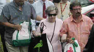 Powerball winner Gloria C. Mackenzie, 84, leaves the lottery office escorted by her son Scott (right) after claiming