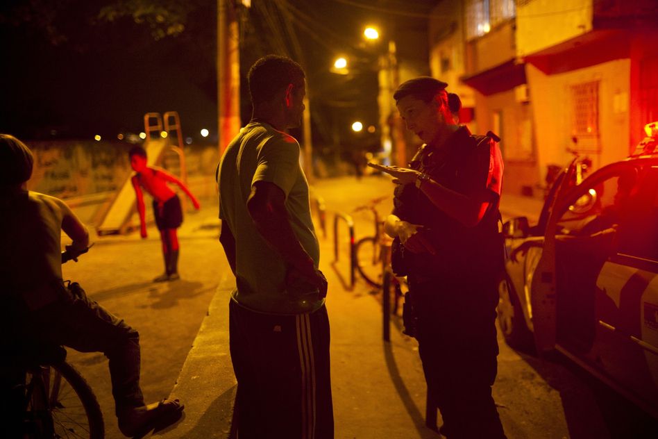 Officer Carla Bon talks with a resident during patrol in Rio's Complexo do Caju. (Lianne Milton for NPR)