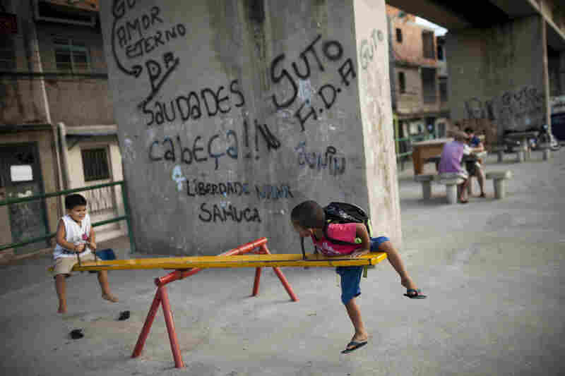 Children in Complexo do Caju, Rio, play near a wall bearing graffiti messages for dead drug traffickers.