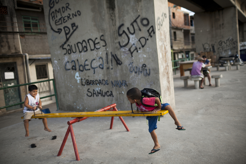 Children in Complexo do Caju, Rio, play near a wall bearing graffiti messages for dead drug traffickers. (Lianne Milton for NPR)
