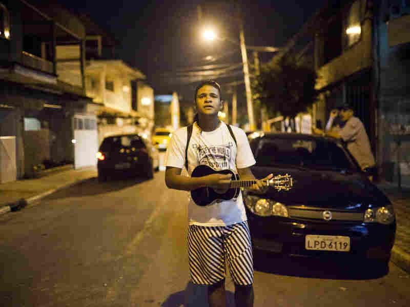 As the streets clear during the evening hours, a young man plays a ukelele-like instrument called a cavaquinho in a residential neighborhood of Mage, where residents can hear evidence of increasing gun power.