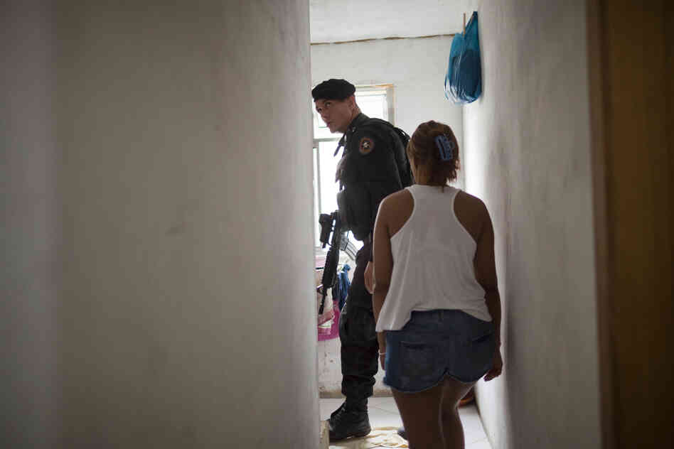 A police officer inspects a resident's home for weapons and drugs in the Parque Alegria favela in Rio in March.