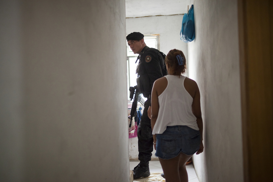 A police officer inspects a resident's home for weapons and drugs in the Parque Alegria favela in Rio in March. (Lianne Milton for NPR)