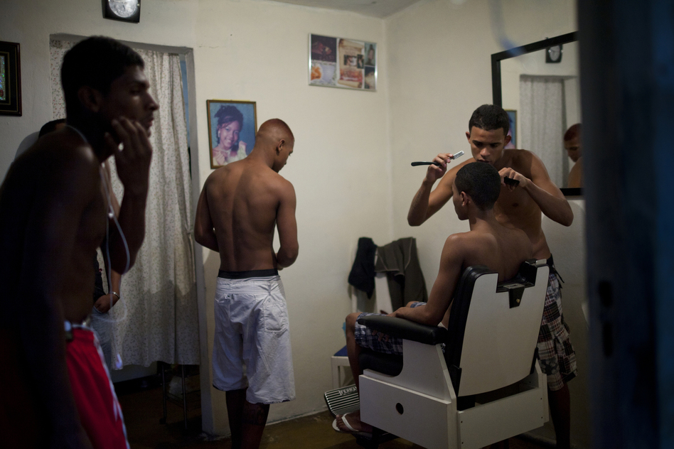 Mateus, 22, who opened a barbershop in his Rio home, shaves his friend's head. Since the pacification program began, more residents say they are moving around more freely in neighboring communities. (Lianne Milton for NPR)