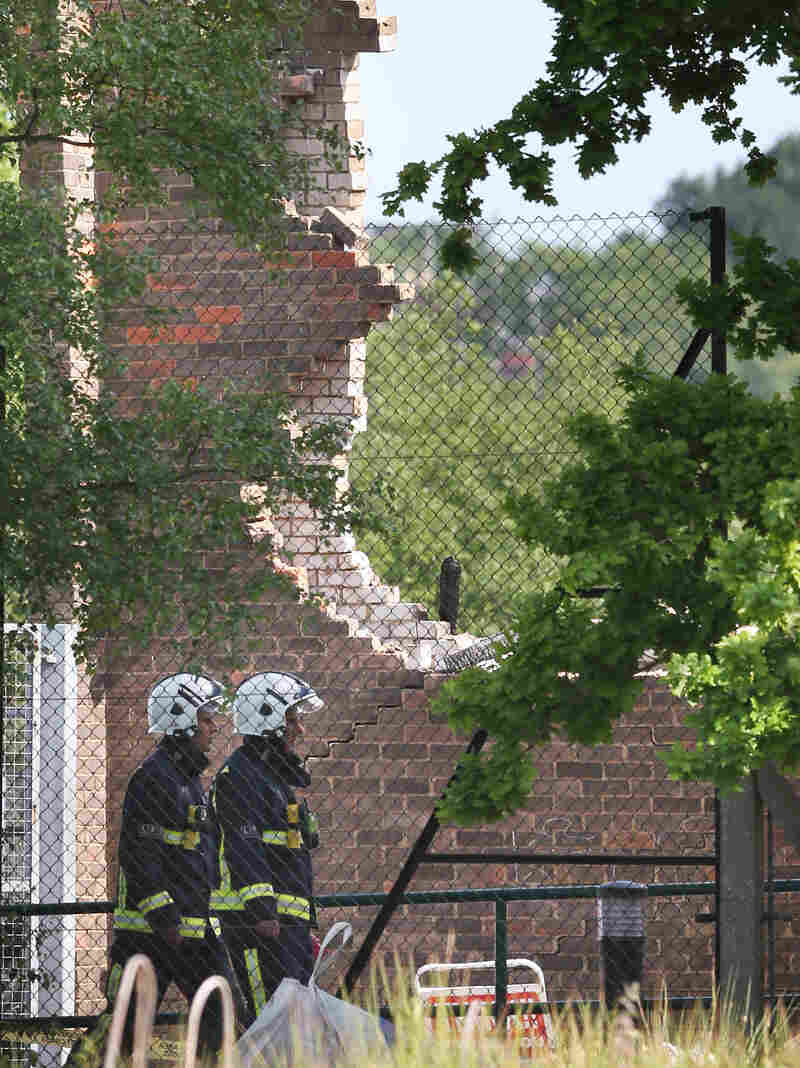 Fire officers walk past the fire-damaged Al-Rahma Islamic Centre in Muswell Hill in London Wednesday. Counter-terrorism officers have been called in amid suspicions that it was a racially motivated attack.