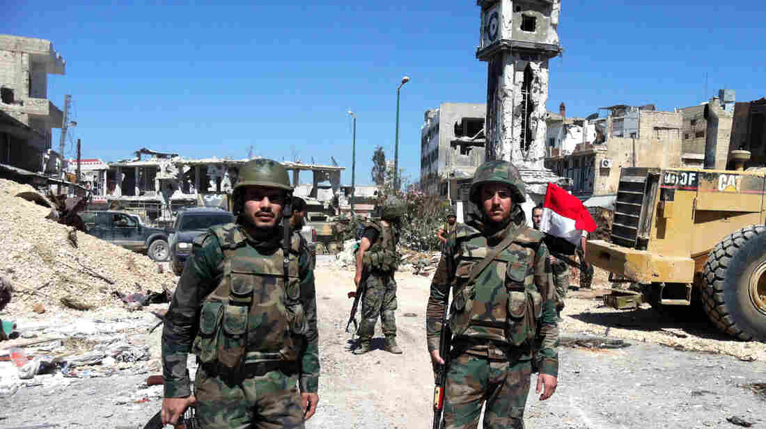 Syrian soldiers stand in the main square of the western city of Qusair. Government troops recaptured the town on Wednesday after rebels had held it for more than a year. It's seen as a significant victory for President Bashar Assad's government.