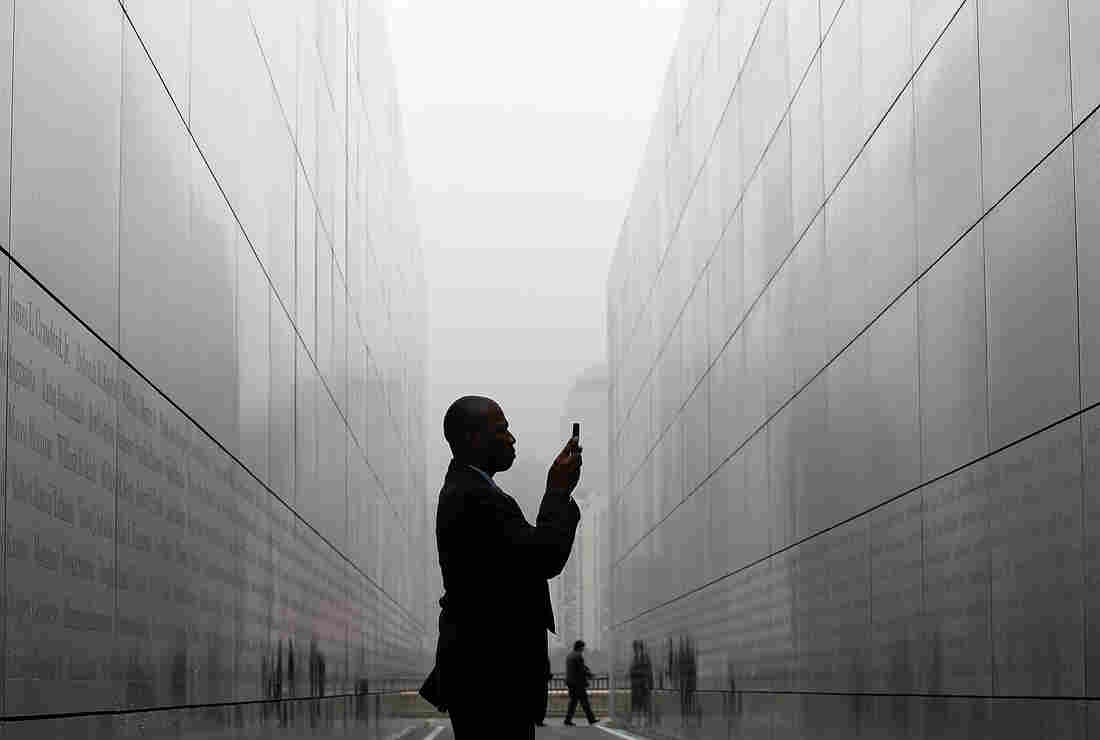 "A man takes a photograph with his cell phone of names on the walls of ""Empty Sky Memorial"" at Liberty State Park in Jersey City, New Jersey. The concrete and steel memoria pays tribute to the 746 citizens of New Jersey who lost their lives on Sept. 11."