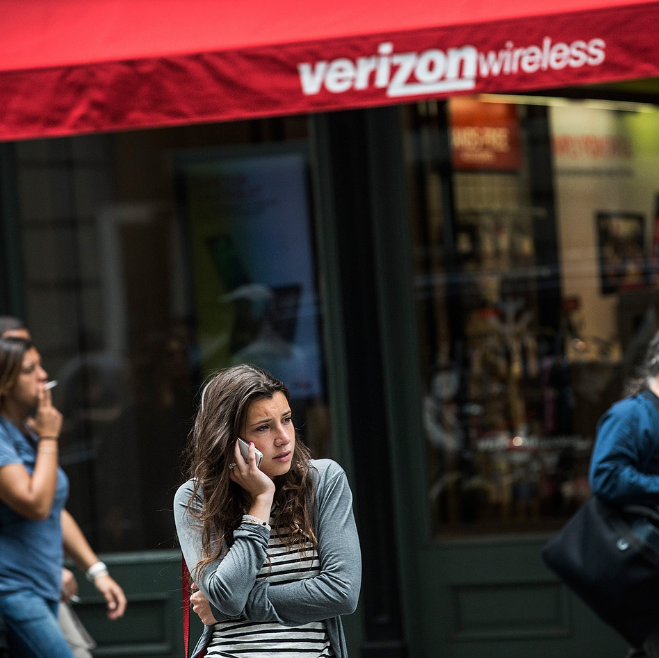 A woman uses her cellphone outside a Verizon Store in Manhattan on Thursday.