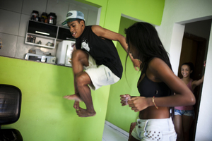 Costa practices passinho with Tais Castro, 14, in the Cidade de Deus neighborhood.  Passinho incorporates more feminine and free movements, which were repressed by Rio's baile funk dance style.