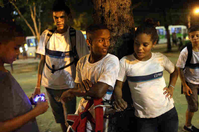 A group of young Cariocas, residents of Rio de Janeiro, listen to passinho music in a neighborhood square.