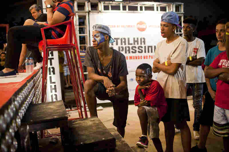 Costa watches other contestants at the Batalha do Passinho. The finals of the dance competition is being televised.