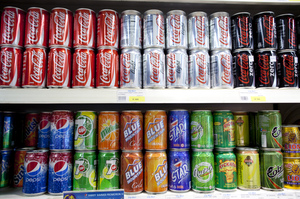 Cans of Coca-Cola at a supermarket in Yangon. On the shelf below is the local cola brand, Star Cola.
