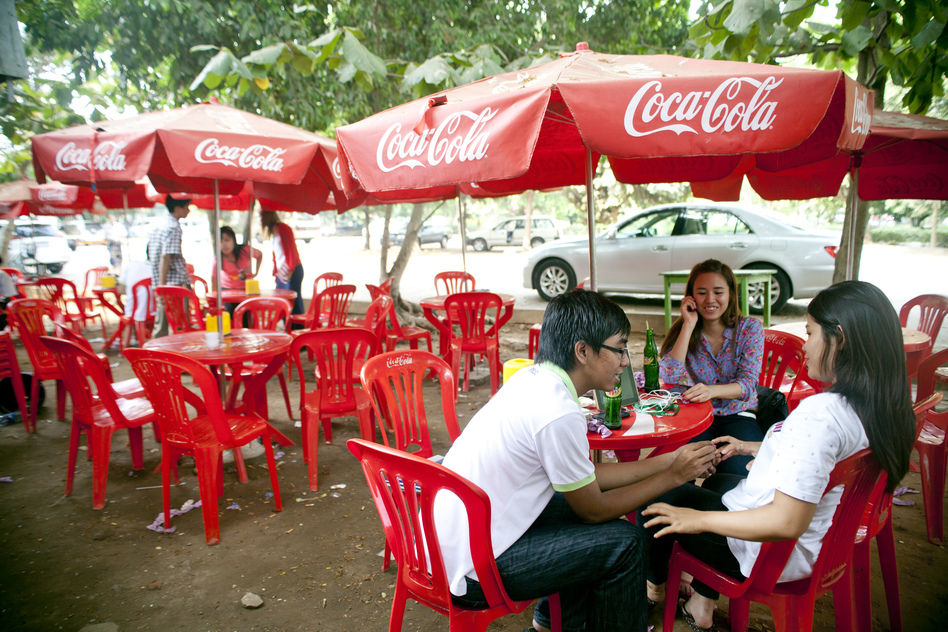 Customers enjoy an afternoon snack and drink at a tea shop near a Myanmar television station in Yangon. (NPR)