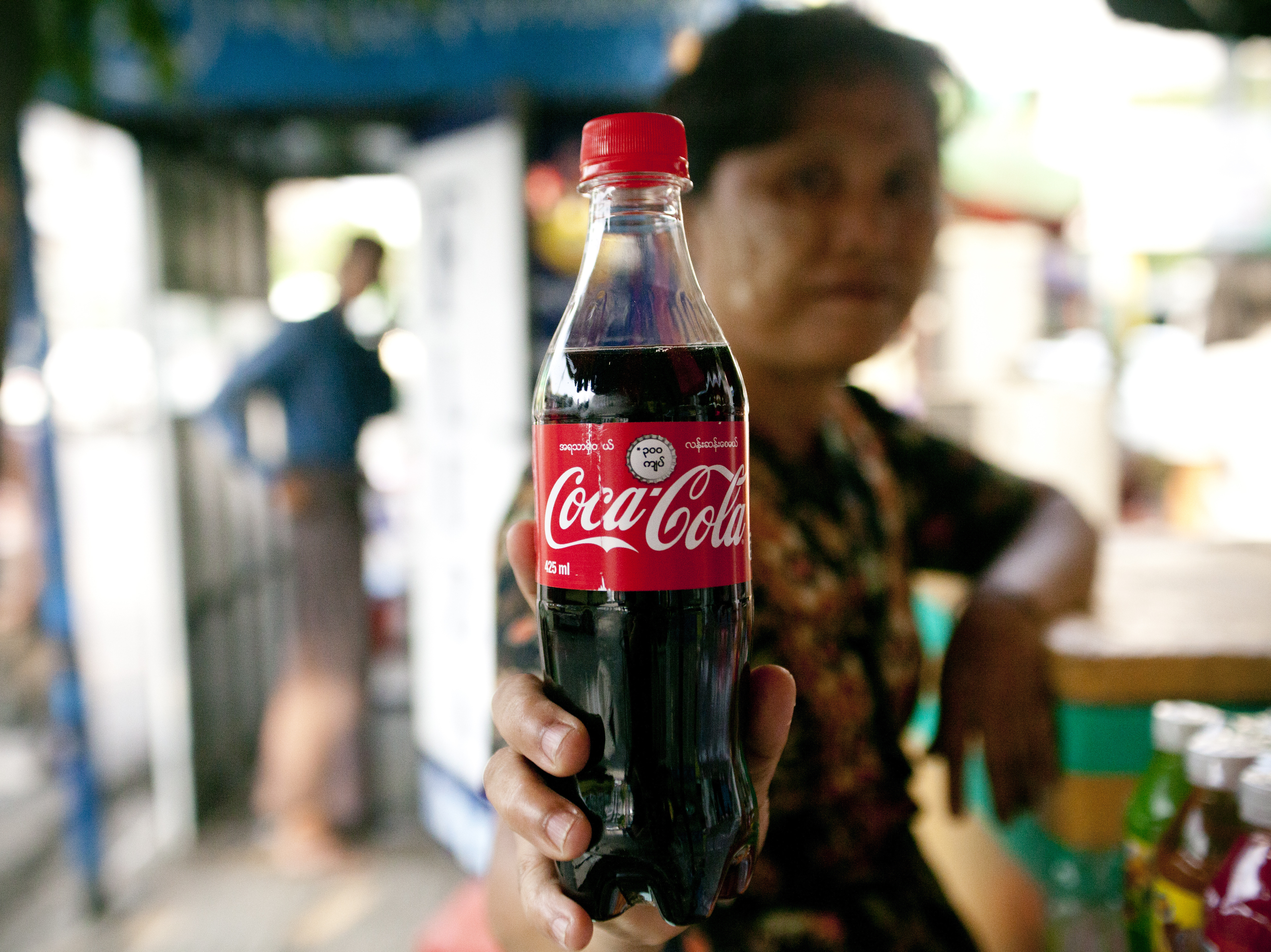 A street vendor holds up a Coca-Cola bottle in Yangon, Myanmar.