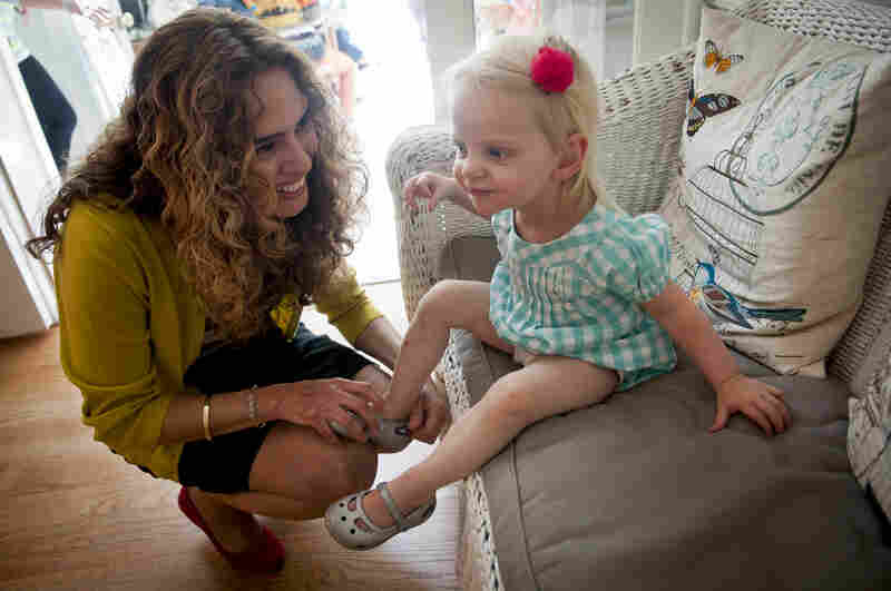 """Morales places a shoe back on Kelly's 1-year-old niece Grace Gipson. Morales, who struggles with multiple sclerosis, says her years with Costello have been """"the happiest years of my life."""""""