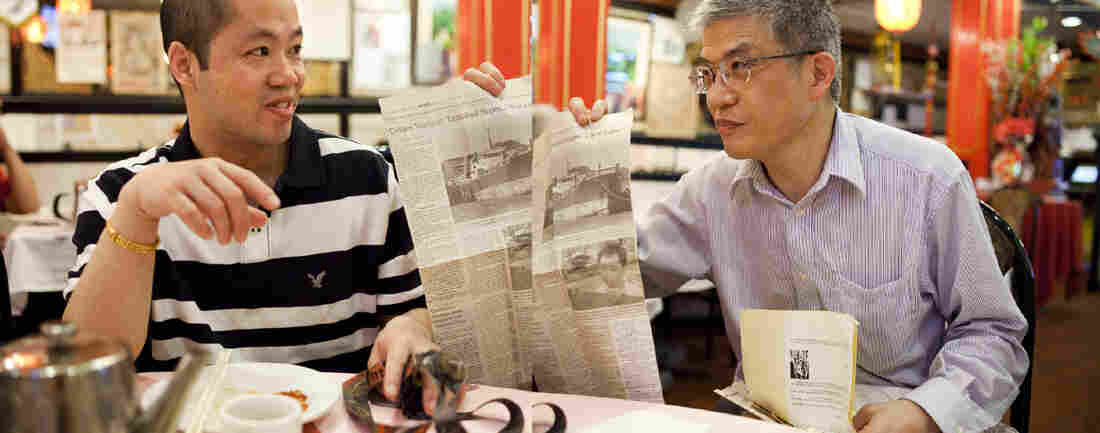 Shengqiao Chen, left, met Zehao Zhou while in prison waiting for asylum. Zhou was his translator. Here, Zhou shares memorabilia with Chen — 20 years after the Golden Venture arrived in the U.S.