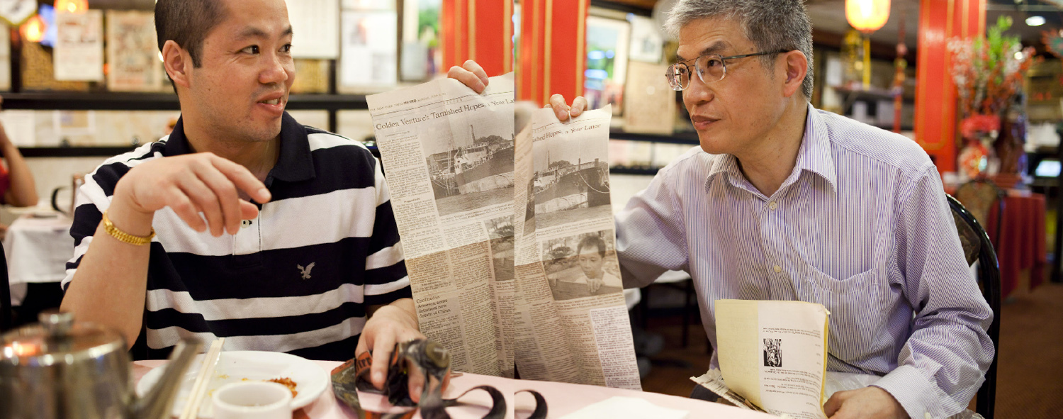 Shengqiao Chen, left, met Zehao Zhou while in prison waiting for asylum. Zhou was his translator. Here, Zhou shares memorabilia with Chen -- 20 years after the Golden Venture arrived in the U.S.