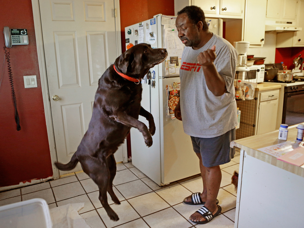 Mike Jackson and his dog Coco at home in Oklahoma City. He says of his medical costs: