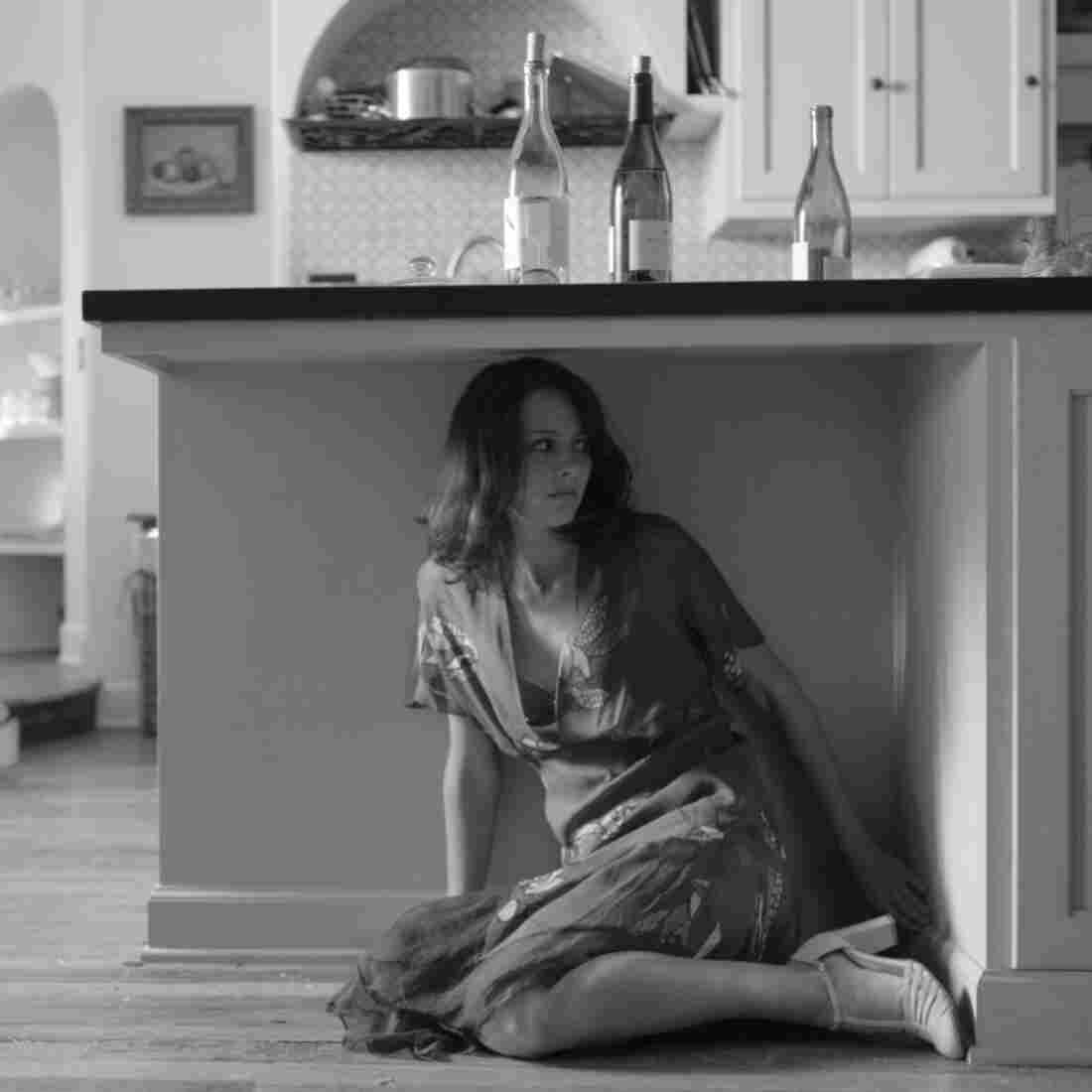 Amy Acker as Beatrice eavesdrops in a scene from Joss Whedon's new film version of Much Ado About Nothing.