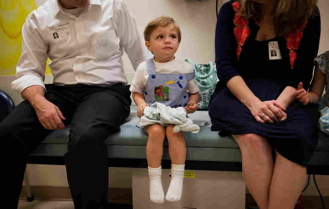 Barton Holmes, 2, sits with his father, Kevin Holmes, and his mother, Catherine McEaddy Holmes, during an appointment at Children's Nation