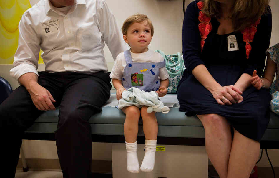 Barton Holmes, 2, sits with his father, Kevin Holmes, and his mother, Catherine McEaddy Holmes, during an appointment at Children's National Medical Center in Washington, D.C.