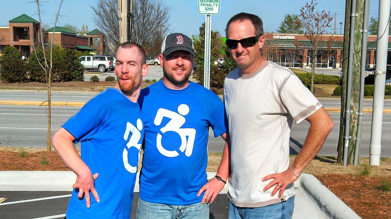 Brendon Hildreth, left, stands with disabilities advocate Don Haines, center, and Vince Andracchio, the owner of Zaxby's in New Bern, N.C., which is already using the new signs.