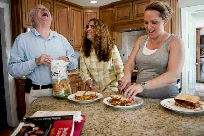 """Fabiola Morales jokes with her father-in-law, Robert F. Costello III, a retired financial adviser, while preparing lunch in the family's kitchen. Kelly Costello's dream is to be able to sponsor Morales and feel """"secure and stable."""""""